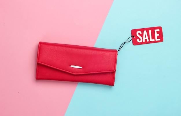 Modische lederbrieftasche mit rotem verkaufsetikett auf rosa blau .. rabatt. minimalismus