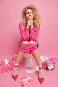 Modische lockige frau sitzt bequem auf der toilettenschüssel hält die hände unter dem kinn überlegt etwas beim stuhlgang genießt eine gemütliche häusliche atmosphäre, umgeben von verschiedenen weiblichen dingen