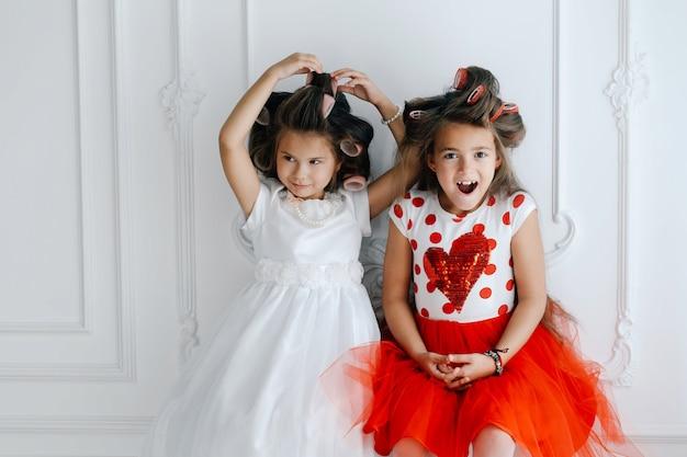 Modische mädchen mit lockenwicklern in luxuriösen, üppigen kleidern