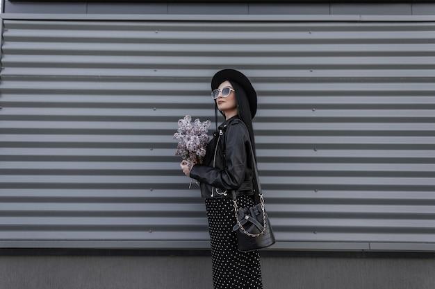 Modische modellfrau in stilvoller sonnenbrille mit hut in schwarzem jugendoutfit steht mit einem strauß lila blumen in der nähe der metallwand in der stadt. attraktives mädchen genießt spaziergang und frische erstaunliche blumen.