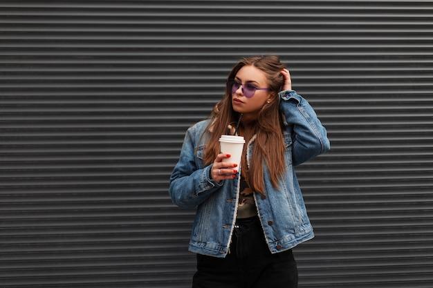 Modische, moderne junge hipster-frau in stilvoller jugendjeanskleidung in trendigen lila gläsern mit einer tasse kaffee, die in der nähe einer metall-vintage-wand in der stadt posiert. amerikanisches mädchen-mode-modell im freien.