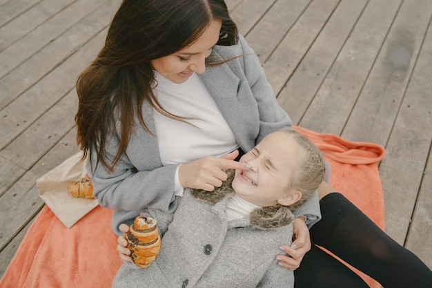 Modische mutter mit tochter. leute auf einem picknick. frau in einem grauen mantel. familie am wasser.