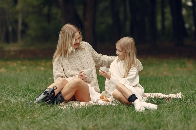 Modische mutter mit tochter. leute sitzen auf einem gras