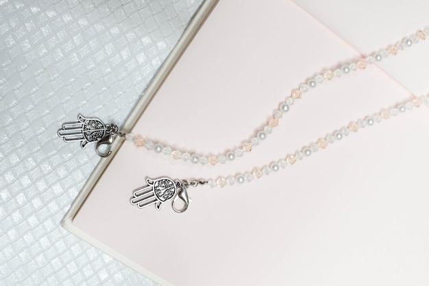 Modische perlenkette mit rosa buchhintergrund