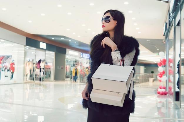 Modische pompöse frau, die mit dem einkaufen auf der mall geht. weibliche hände, die einkaufstüten halten