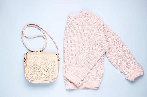 Modische rosa pastell gestrickte pullover ledertasche auf einem grauen tisch. draufsicht