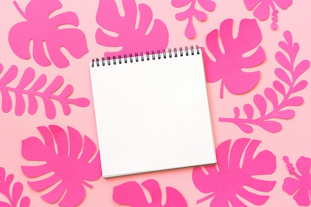 Modische rosa tropische blätter des papiers und offenes notizbuch auf rosa hintergrund, kreative papierkunst