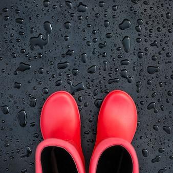 Modische rote gummistiefel auf der schwarzen nassen oberfläche bedeckt mit regentropfen.