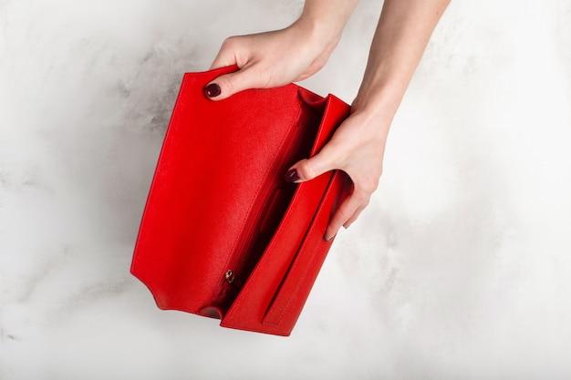 Modische rote weibliche handtasche auf weißer granitbeschaffenheit