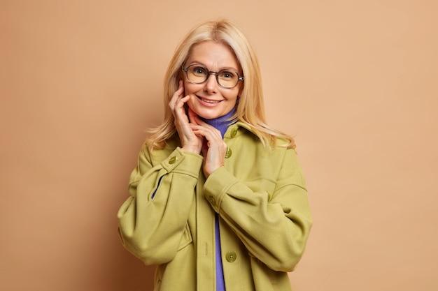 Modische schöne blonde frau berührt gesicht sanft sieht direkt hat gesunde haut und minimales make-up in stilvolle kleidung gekleidet.