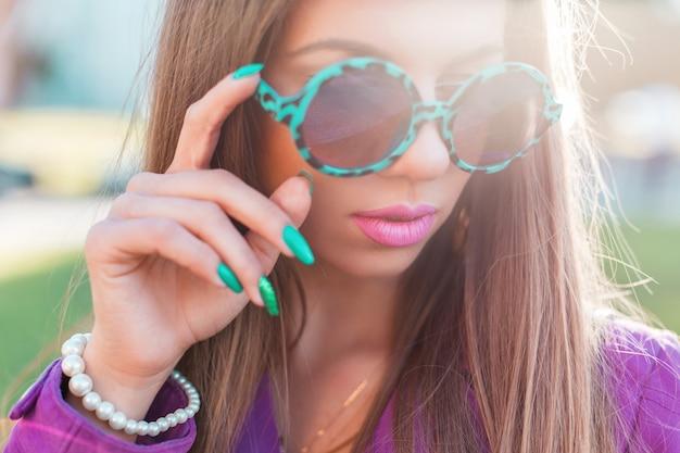 Modische schöne frau in einer rosa jacke mit sonnenbrille, die im park aufwirft.