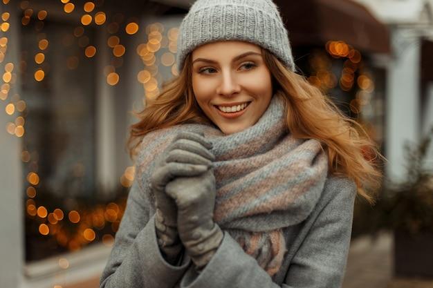 Modische schöne glückliche frau mit einem lächeln in strickkleidung mit einer strickmütze in einem grauen mantel in den winterferien auf der straße. festliche lichter hintergrund