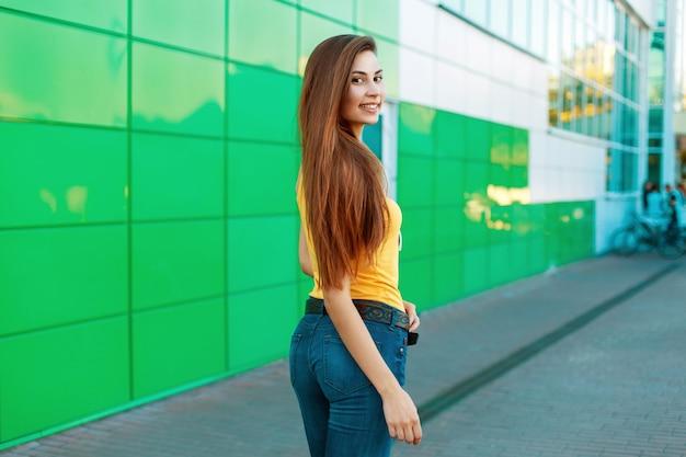 Modische schöne glückliche frau mit einem lächeln nahe grüner wand