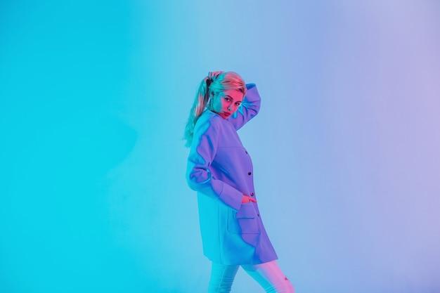 Modische schöne junge blonde frau in stilvoller geschäftskleidung auf buntem licht im kreativstudio