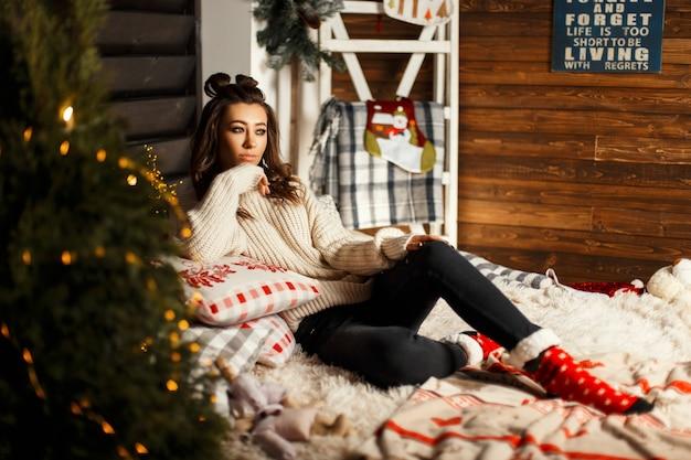Modische schöne junge frau in einem gestrickten vintage-pullover mit roten weihnachtssocken liegt auf dem bett