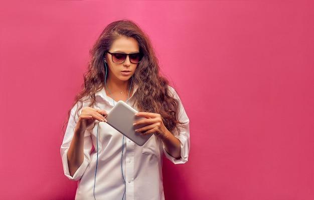 Modische schöne junge frau in einem weißen hemd in den gläsern mit kopfhörern, die eine weiße tablette in den händen auf einer rosa bunten wand halten