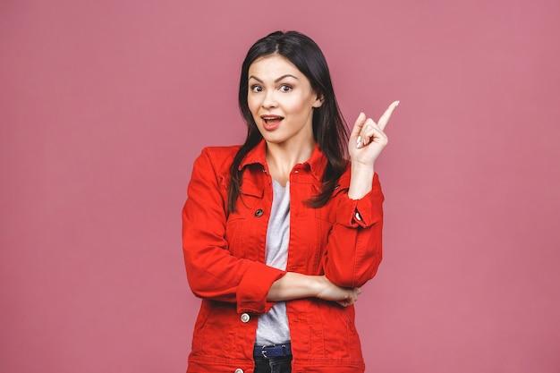 Modische schöne junge verblüffte frau, die finger nach oben zeigt. über rosa isoliert.