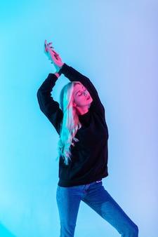 Modische schöne sinnliche blonde frau in schwarzem hoodie mit stylischer blue jeans auf mehrfarbigem neonrosalicht im studio