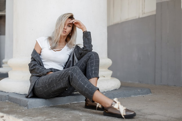 Modische schöne stilvolle frau in einem grauen mantel und in der stilvollen hose mit schuhen, die nahe einer weißen säule auf der straße sitzen