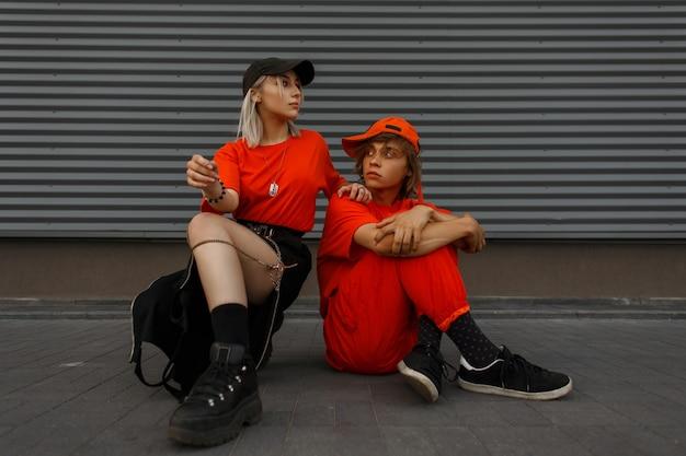 Modische schöne stilvolle junge paare mit mützen in modischen orangefarbenen kleidern mit modeschuhen sitzen auf der straße in der nähe der metallgrauen wand