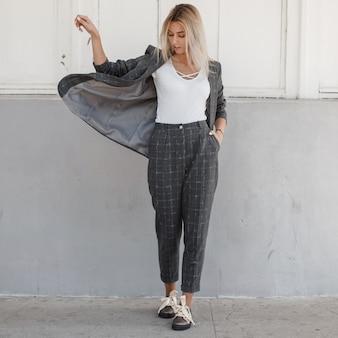 Modische schöne stilvolle modellfrau in einer grauen jacke mit einem t-shirt und einer stilvollen hose, die auf der straße gehen. modischer strenger stil