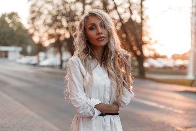 Modische schöne stilvolle modellfrau mit natürlichem make-up geht auf der straße in der stadt bei sonnenuntergang