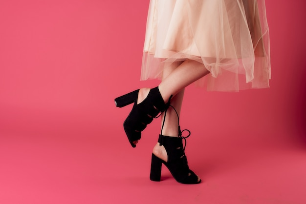 Modische schuhe der damenfüße bezaubern rosa hintergrundeinkäufe. hochwertiges foto