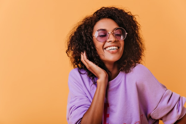 Modische schwarze frau, die bunt mit fröhlichem lächeln aufwirft. optimistisches afrikanisches mädchen im lila pullover