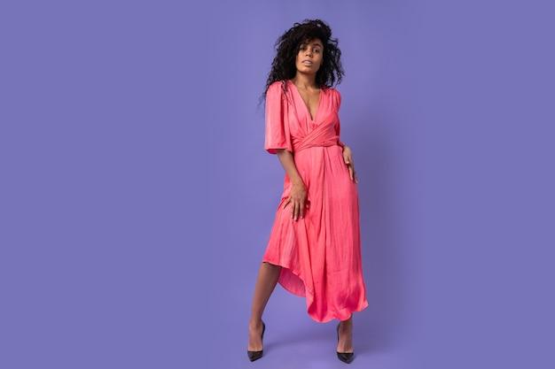 Modische selbstbewusste frau mit den lockigen haaren, die über lila wand aufwerfen. elegantes partykleid tragen. frühlingsmode-look. volle länge.