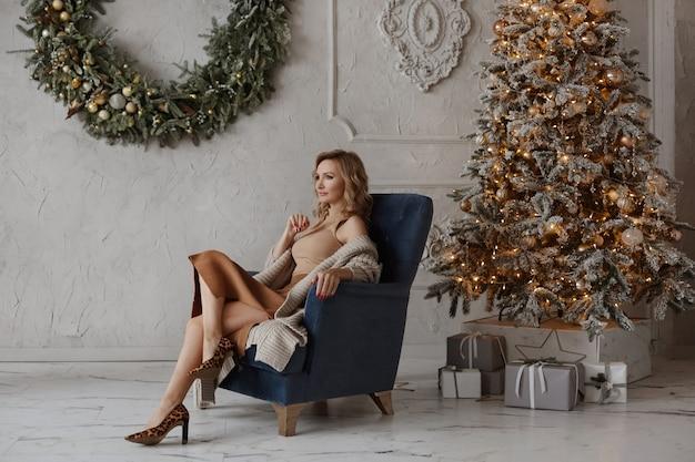 Modische sinnliche frau mit stilvollem make-up posiert in der nähe des weihnachtsbaums im luxuriösen interieur