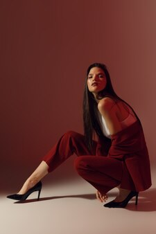 Modische sitzende frau posiert, stilvolle fotografie mit farbstudiolicht, vertikales foto. hochwertiges foto