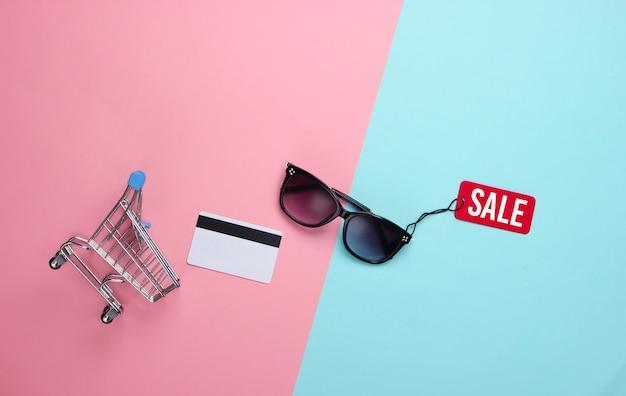 Modische sonnenbrille mit rotem verkaufsetikett, bankkarte, einkaufswagen auf rosa blau. rabatt. minimalismus