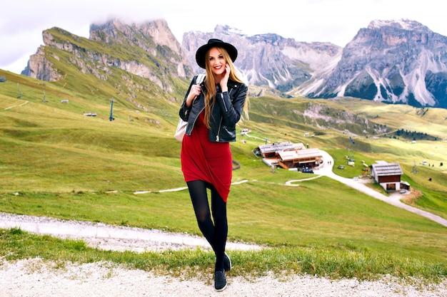 Modische stilvolle frau, die im luxusgebirgs-italienischen dolomitengebirgsresort, im trendigen touristischen ausstattungshut und im rucksack, urlaubsstimmung aufwirft.