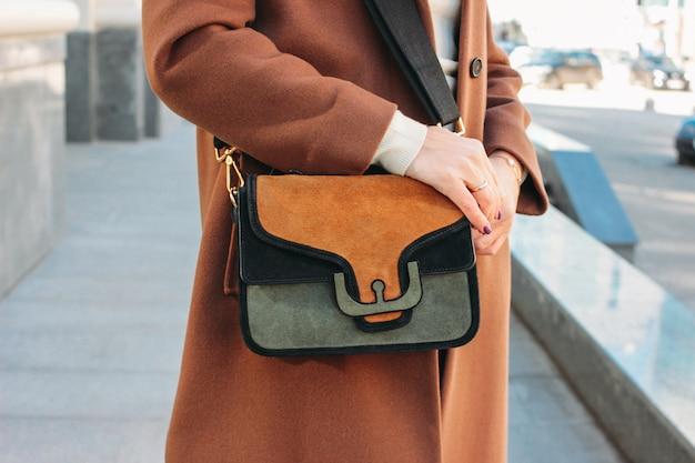 Modische stilvolle frau in einem beige mantel mit einer modischen wildledertasche