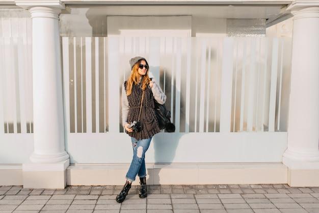 Modische stilvolle joufylfrau, die auf sonnenschein auf straße kühlt. hübsche junge frau in sonnenbrille, warmer winterwollpullover, strickmütze mit kamera, rucksack. fröhliche stimmung, lächelnd.
