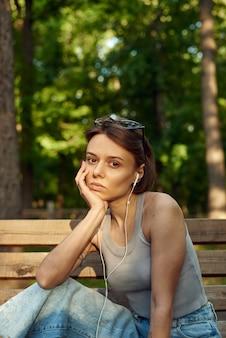 Modische stilvolle junge frau, die musik auf verdrahteten kopfhörern beim sitzen auf einer parkbank hört.