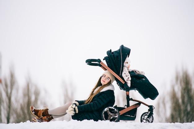 Modische stilvolle junge mutterruhe mit ihrer tochter, die im winter im kinderwagen im park draußen sitzt.