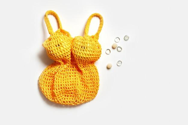 Modische trendige gelbe lebensmittel-netzbeutel auf weißem hintergrund. nicht standard. rette den planeten, indem du plastik aufgibst