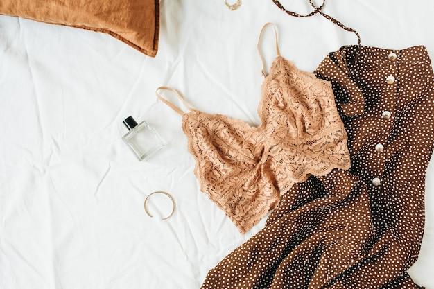 Modische trendige unterwäschekomposition. bh, parfüm, abendkleid auf weißem leinen