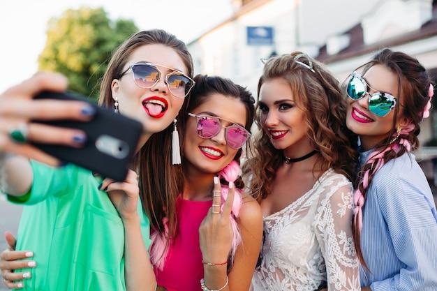 Modische und schöne beste freundinnen in gläsern, posieren tun allgemein selbst für soziale netzwerke