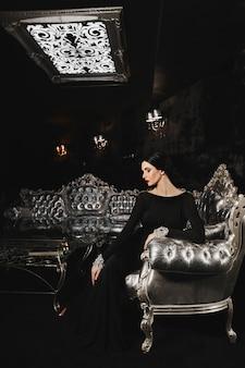 Modische und sexy brünette modelfrau mit perfektem körper und roten lippen im schwarzen abendkleid mit sitz auf dem silbernen sofa im modernen luxus-interieur
