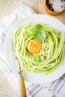 Modische vegane lebensmittelrezepte, käse-zucchini-spaghettiteigwaren mit eigelb mit parmesankäse, olivenöl und basilikumblättern, leichtbetonoberfläche