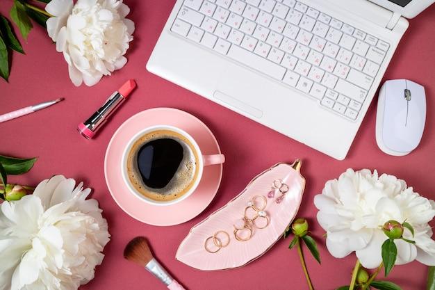 Modische weibliche arbeitsfläche flach mit schönen weißen pfingstrosenblumen, kosmetik und kaffeetasse
