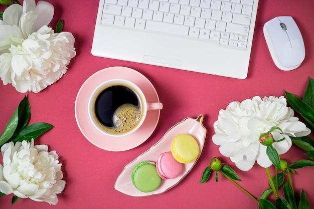 Modische weibliche arbeitsfläche flach mit schönen weißen pfingstrosenblumen und kaffeetasse