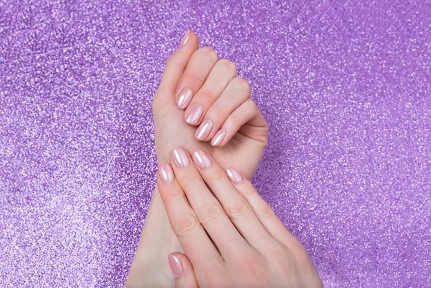 Modische weibliche maniküre, zarte rosa farbe. glänzendes lila