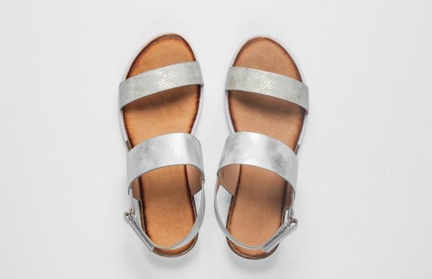 Modische weibliche sandalen auf weiß.