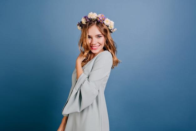 Modische weiße frau im hellblauen outfit, die spaß im studio hat