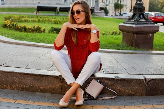 Modische weiße frau im pullover, der auf der straße im stadtzentrum sitzt. stilvolle sonnenbrille. herbststimmung.