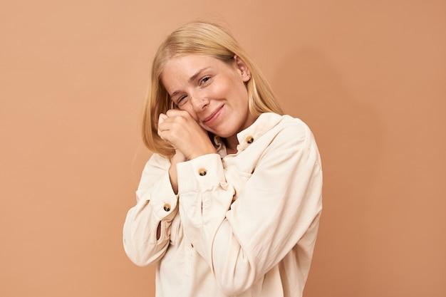 Modische zufriedene teenagerin mit nasenpiercing und sommersprossen, die hände unter der wange halten, geneigten kopf, nach vorne schauendes glückliches lächeln, träumen von etwas angenehmem