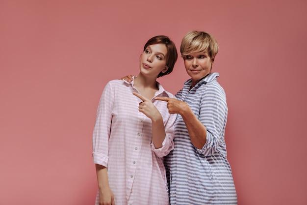 Modische zwei frauen mit kurzer stilvoller frisur in gestreiften kühlen kleidern, die zeigen, um für text auf rosa lokalisiertem hintergrund zu platzieren.